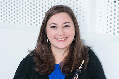 Jenna Sehmann standing with instrument in front of white patterned background